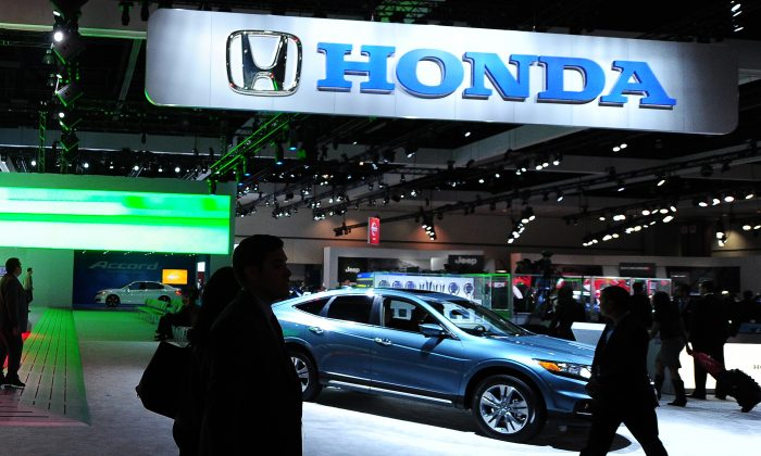 Visitors walk past the Honda display at the 2012 Los Angeles Auto Show in Los Angeles, California on media preview day, November 28, 2012. (Robyn Beck/AFP/Getty Images)