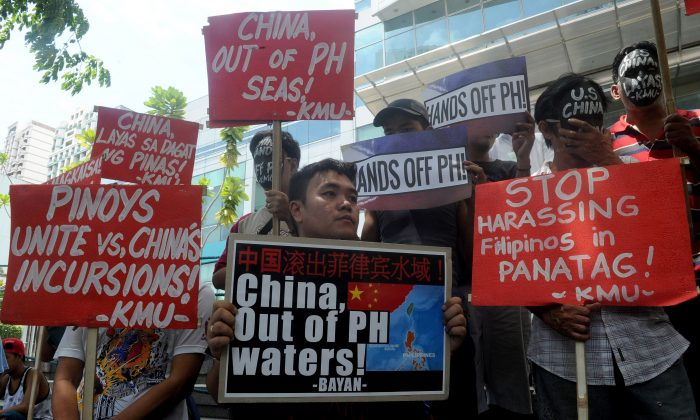Protesters hold a rally in front of the Chinese Consulate in Manila's financial district on July 7, denouncing the Chinese regime's claims to the South China Sea. Chinese authorities may soon start the second phase of island building in the disputed waters. (Jay Directo/AFP/Getty Images)