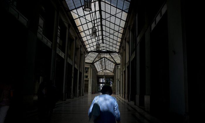 A man passes through an arcade with shuttered shops in central Athens, Tuesday, July 14, 2015. ((AP Photo/Petros Giannakouris)