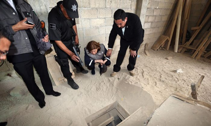 "Mexico's attorney general authorities inspect the exit of the tunnel they claim was used by drug lord Joaquin ""El Chapo"" Guzman to break out of the Altiplano maximum security prison in Almoloya, west of Mexico City, on July 12, 2015. (Mexico's Attorney General's Office via AP)"