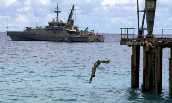 Off duty Australian Navy personnel enjoy some relaxation diving into the Indian ocean near by a Australian Navy boat used to intercept asylum seekers, docked at the Flying Fish Cove, Christmas Island, Australia.