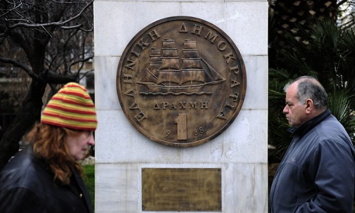 People walk past a monument featuring a replica of the last edition of the Greek currency, the drachma, in the center of Athens in February. If Greek voters decide to leave the euro currency, it would mean a return to the drachma. (ARIS MESSINIS/AFP/Getty Images)
