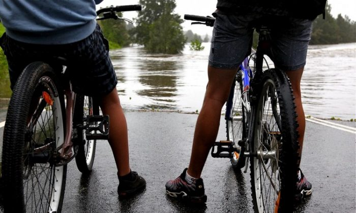 Locals look on as the Hawkesbury River rises completely covering the Yarramundi Bridge, on March 3, 2012, in Richmond, Australia. (Marianna Massey/Getty Images)