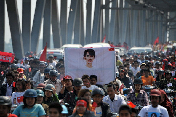 Supporters of Burmese opposition leader Aung San Suu Kyi carry a portrait of her as they follow her on the Sagaing bridge ahead of a campaign rally in Sagaing, northern Myanmar on March 4. (Soe Than Win/AFP/Getty Images)