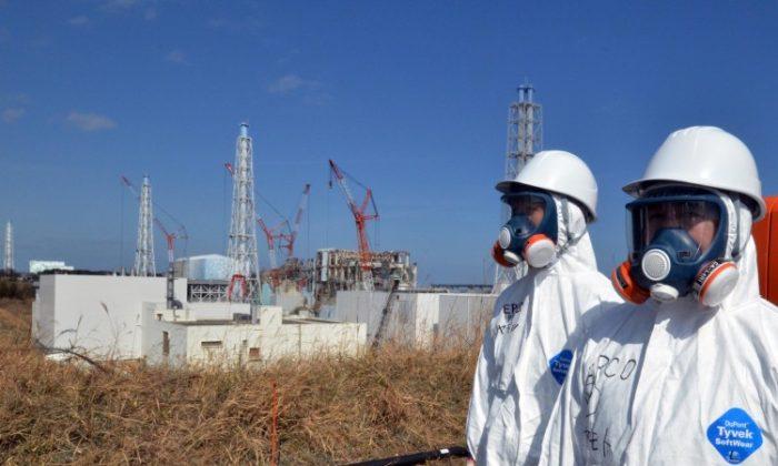 Workers are standing near the stricken Fukushima Daiichi nuclear power plant in Okuma, Fukushima prefecture in late February. (Yoshikazu Tsuno/AFP/Getty Images)