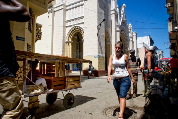 Cubans walk next to Our Lady of Charity church, occupied by 13 Cuban oppositors on March 14, 2012 in Havana. (Adalberto Roque/AFP/Getty Images)