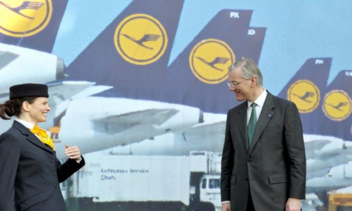 German airline Lufthansa's CEO Christoph Franz poses for photographers with a cabin crew member during the results press conference in the central German city of Frankfurt am Main on March 15, 2012. (Boris Roessler/AFP/Getty Images)