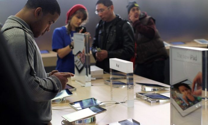 People purchase the new iPad which went on sale around the world Friday on March 16, in Apple's flagship store in New York City. (Spencer Platt/Getty Images)