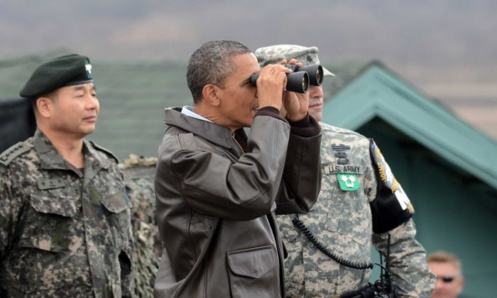 U.S. President Barack Obama uses binoculars to look at North Korea from the Observation Post Ouellette in the Demilitarized Zone which separates the two Koreas in the inter-Korean truce village of Panmunjom on March 25, 2012 in Panmunjom, South Korea. (Yonhap News via Getty Images)