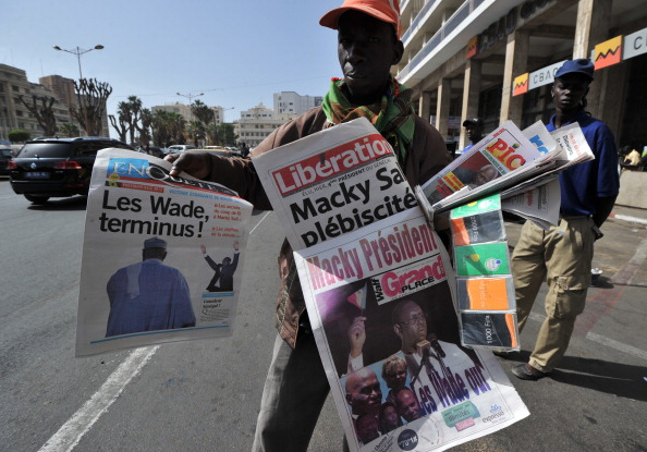A street vendor sells Senegalese newspapers with front page descriptions of Sunday's presidential elections in Dakar. (Issouf Sanogo/AFP/Getty Images)
