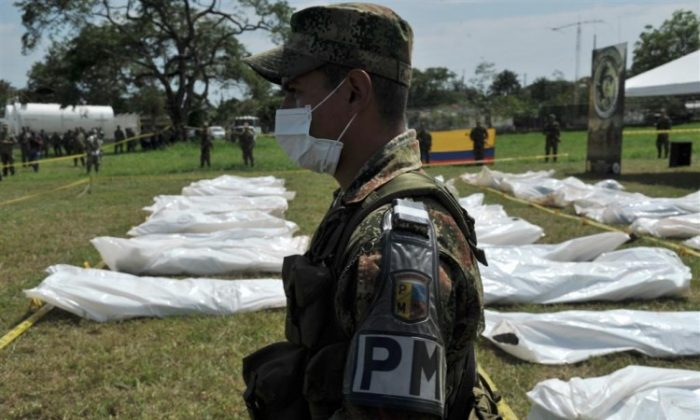 A military police officer stands guard at the Apiay air base in Colombia next to the corpses of FARC guerrillas killed in a joint operation by the Colombian army, air force and police on March 27. (Guillermo Legaria /AFP/Getty Images)