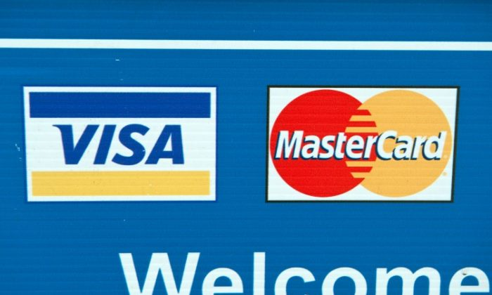 Visa and MasterCard credit card logos are seen on a sign in Washington on March 30, 2012. Starting Jan. 27, merchants have the ability to charge a checkout fee for customers using such credit cards. (Nicholas Kamm/AFP/Getty Images)