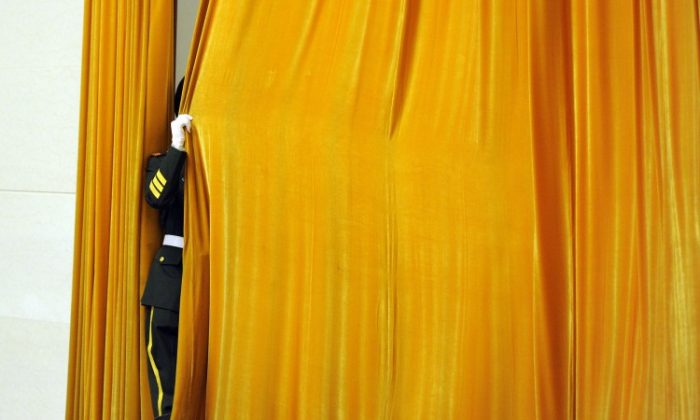 A Chinese guard shuts a drape prior to a welcoming ceremony at the Great Hall of the People in Beijing, April 9, 2012. China reassigned a large number of high-ranking military officers and the process is not transparent. (Liu Jin/AFP/Getty Images)