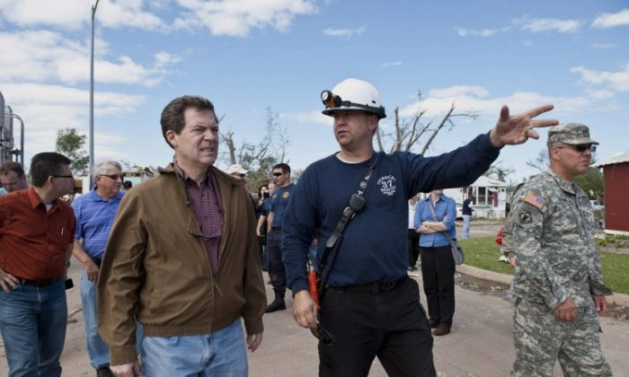 Kansas Gov. Sam Brownback (center L) and John Troyer (C), captain of the Sedgwick County Fire Department, tour Pinaire Mobile Home Park on April 15 in Wichita, Kan. The storms were part of a massive system that affected areas from Northern Nebraska and Iowa south through Oklahoma. (Julie Denesha/Getty Images)