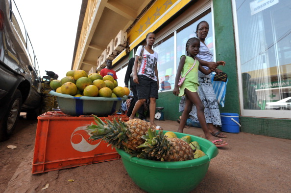 People walk by fruits to buy in a street of Bissau, the capital of Guinea-Bissau, on April 17, 2012. (Seyllou/AFP/Getty Images)