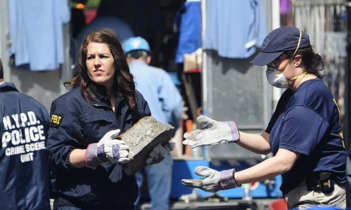 New York police and FBI agents remove pieces of concrete after digging up a basement believed to contain clues to the unsolved disappearance 33 years ago of 6-year-old Etan Patz, in New York. On Wednesday a man from New Jersey confessed to the murder of the boy. (EMMANUEL DUNAND/AFP/Getty Images)