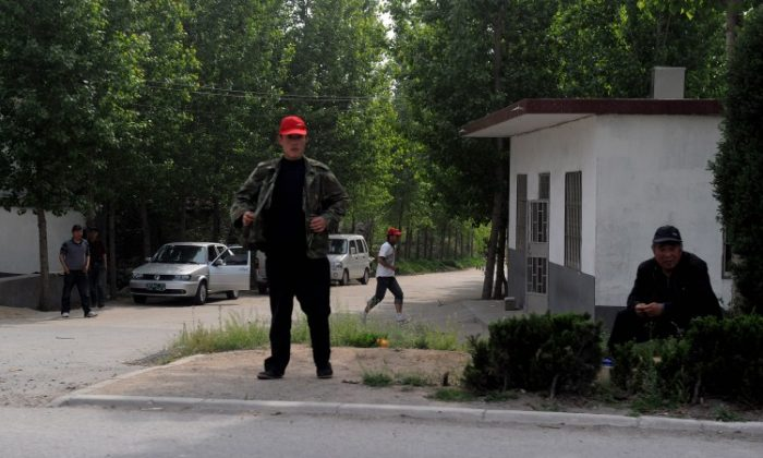 Plainclothes security monitor the entrance to Dongshigu Village, in Shandong Province on April 28, where blind activist Chen Guangcheng lives. More than US$31.6 million has been spent since 2008 to monitor Chen and his family.(Mark Ralston/AFP/GettyImages)