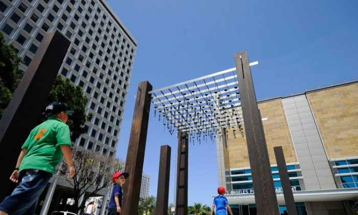 Children walk under an art installation outside the new LAPD Metropolitan Detention Center. Built at the site where a parking kiosk was burned in front of LAPD's Parker Center during the 1992 Los Angeles riots, the installation features more than 100 dangling metal bells, with words like 'Freedom' and 'Justice' suspended in the breeze. (Kevork Djansezian/Getty Images)