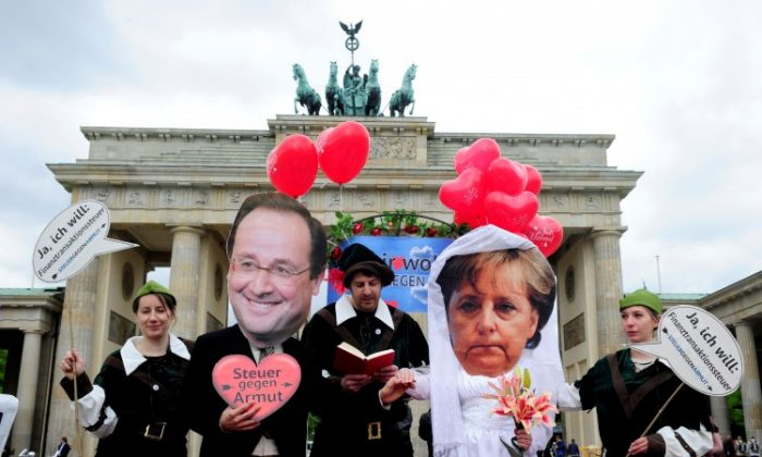 Activists wear masks featuring German chancellor Angela Merkel (2nd R) and incoming French Socialist President François Hollande (2nd L) as they perform a fake marriage in front of the Brandenburg Gate in Berlin, on May 7. (John Macdougall/AFP/GettyImages)