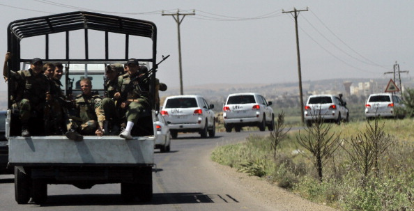 Syrian soldiers escort a U.N. peace observers convoy on its way to the restive southern city of Daraa just before a roadside bomb attack targeted them on May 9, 2012. (Louai Beshara/AFP/GettyImages)