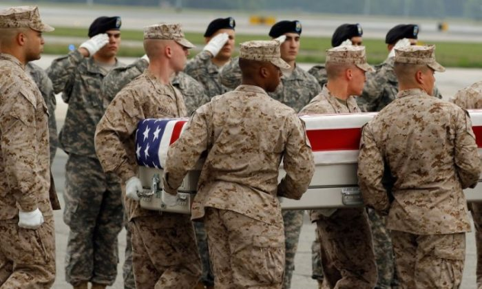 A U.S. Marine Corps carry team moves the flag-draped transfer case with the remains of U.S. Marine Corps Sgt. John Huling across the tarmac at Dover Air Force Base in Dover, Del., May 9. Assigned to 7th Engineer Support Battalion, 1st Marine Logistics Group, and 1st Marine Expeditionary Force, out of Camp Pendleton, Calif., Huling died May 6 in the Helmand province of Afghanistan after being shot by a person wearing an Afghan National Army uniform. Huling's death is still under investigation. (Chip Somodevilla/Getty Images)
