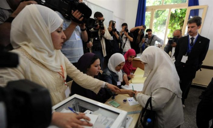 Algerians vote in a polling station in the capital Algiers as the head of the European Mission election observer mission, Jose Ignacio Salafranca (R) visits the station. (AFP/GettyImages)