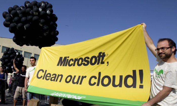 """Activists from Greenpeace hold a banner with the slogan """"Microsoft, clean our cloud"""" during a protest in Tel Aviv during a Microsoft exhibition on April 22.(JACK GUEZ/AFP/GettyImages)"""