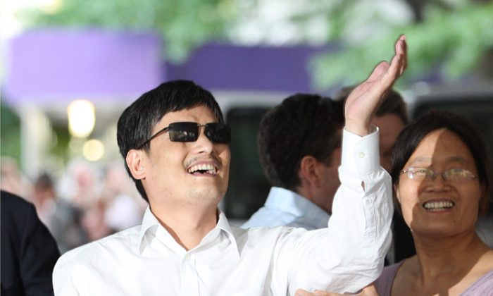 Chen Guangcheng gestures beside his wife Yuan Weijing before making remarks to the media, upon his arrival at New York University campus on May 19. (Andy Jacobsohn/Getty Images)