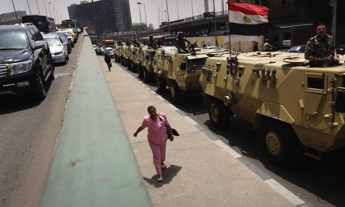 A pedestrian walks past an Egyptian army convoy patrolling the streets on May 22, 2012 in Cairo, Egypt. (John Moore/Getty Images)