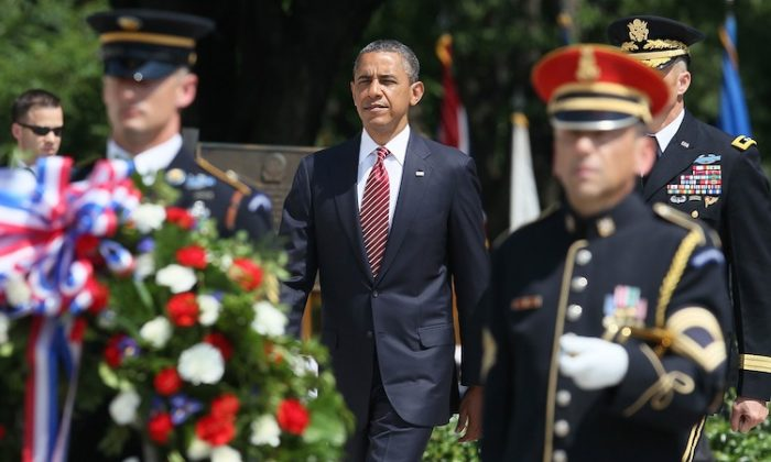 U.S. President Barack Obama (C) walks up to lay a commemorative wreath during a ceremony on Memorial Day at the Tomb of the Unknowns at Arlington National Cemetery on May 28, 2012 in Arlington, Virginia. For Memorial Day President Obama is paying tribute to military veterans past and present who have served and sacrificed their lives for their country. (Mark Wilson/Getty Images)