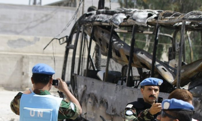 UN observers photograph the scene by a bombed bus outside a Shiite holy shrine in the Sayyida Zeinab suburb of Damascus on June 14, 2012. (LouaiBesgara/AFP/GettyImages)