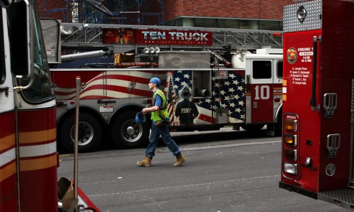 A Ground Zero construction worker walks by fire trucks on June 14, in New York City. (Spencer Platt/Getty Images)