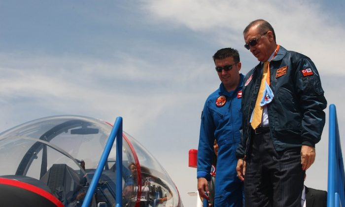 Turkish Prime Minister Recep Tayyip Erdogan (L) gets into the cockpit of a Hurkus (Freebird) outside Ankara on June 27, 2012. (Adem Atan/AFP/GettyImages)