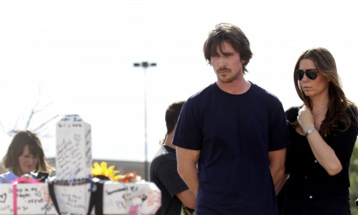 Actor Christian Bale and wife Sibi Blazic visit the memorial across the street from the Century 16 movie theater July 24 in Aurora, Colo. The memorial was created for the victims of the mass shooting that occured at the theater last Friday. James Holmes, 24, is accused of killing 12 people and injuring 58 at a screening of the new Batman film. (Joshua Lott/Getty Images)