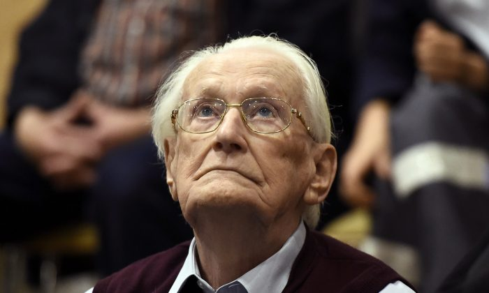 94-year-old former SS sergeant Oskar Groening looks up as he listens to the verdict of his trial Wednesday, July 15, 2015 at a court in Lueneburg, northern Germany. Groening, who served at the Auschwitz death camp was convicted on 300,000 counts of accessory to murder and given a four-year sentence. (Tobias Schwarz/Pool Photo via AP)