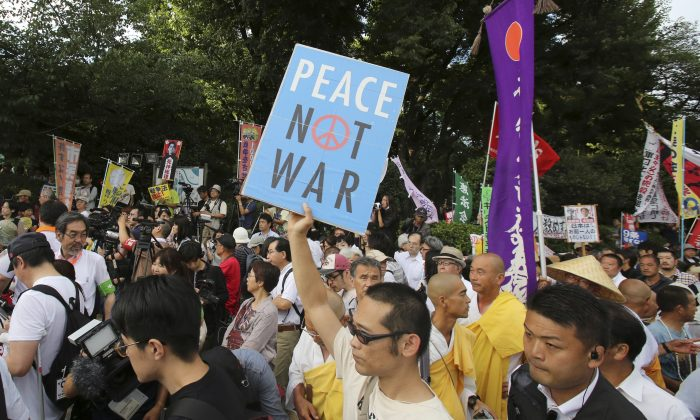 Protesters stage a rally in front of the Parliament building after a parliamentary committee approved legislation that would expand the role of Japan's military in Tokyo, Wednesday, July 15, 2015. (AP Photo/Shuji Kajiyama)