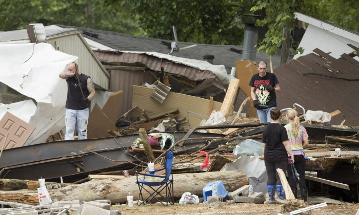 Residents of a mobile home park look for belongings after deadly flooding in Flat Gap, Ky., Tuesday, July 14, 2015. (AP Photo/David Stephenson)