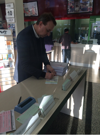 Lawyer Kerry Gore prepares package for an express delivery of the criminal complaint against Jiang Zemin at a post office in New Zealand. (Courtesy of Kerry Gore)