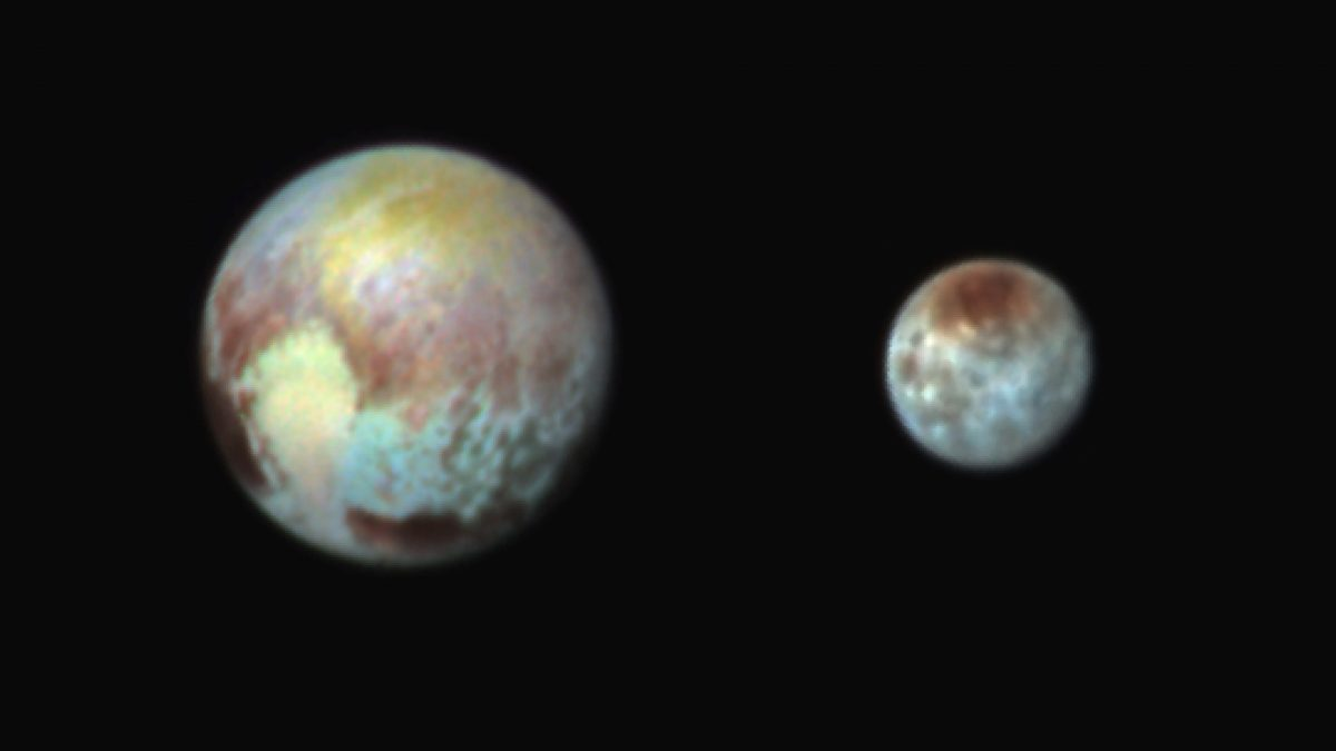 This Monday, July 13, 2015 combination image released by NASA shows Pluto, left, and its moon, Charon, with differences in surface material and features depicted in exaggerated colors made by using different filters on a camera aboard the New Horizons spacecraft. In this composite false-color image, the apparent distance between the two bodies has also been reduced. (NASA/APL/SwRI via AP)