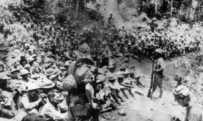 FILE - In this 1942 file photo provided by U.S. Marine Corps, Japanese soldiers stand guard over American war prisoners just before the start of the Bataan Death March following the Japanese occupation of the Philippines. (U.S. Marine Corps via AP, File)