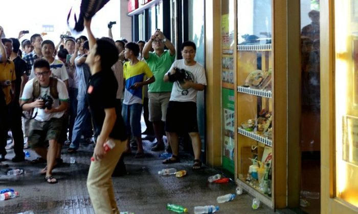 A group of protesters pelt a Japanese restaurant (R) with plastic bottles as they attend a rally against Japan's claim of islands known as Senkaku in Japan and Diaoyu in China, in Hangzhou in China's Zhejiang province on August 19, 2012. (STR/AFP/GettyImages)