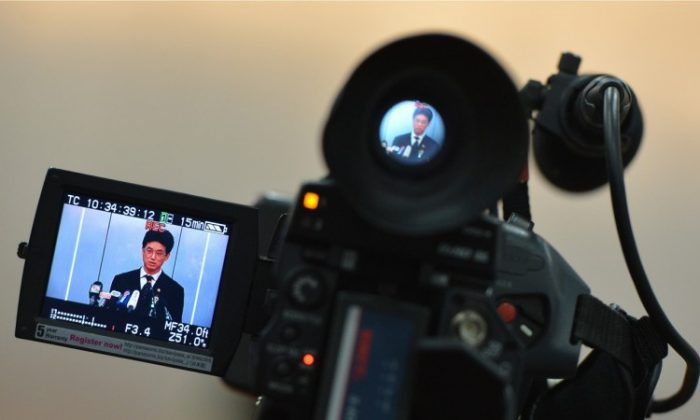 A video camera shows Chengdu People's Intermediate court spokesman Yang Yuquan delivering the verdict of the ex-police chief Wang Lijun to the press in Chengdu, on Sept. 24, 2012.Although Hu, Wen, and Xi have gradually gained the upper hand, they have chosen not to hold Jiang's faction accountable for organ harvesting. (Mark Ralston/AFP/Getty Images)