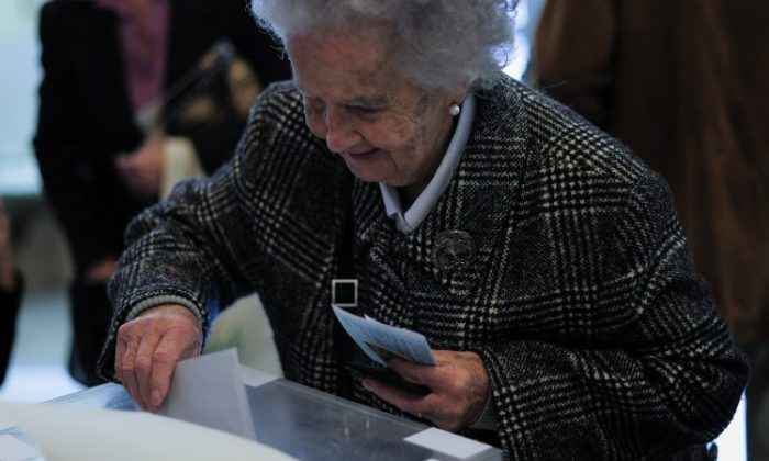 An elderly woman casts her ballot for regional elections in Barcelona on Nov. 25. (Josep Lago/AFP/Getty Images)