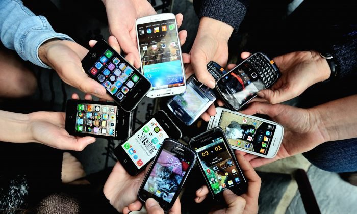 People show their smartphones on December 25, 2013 in Dinan, northwestern France. (Philippe Huguen/AFP/Getty Images)