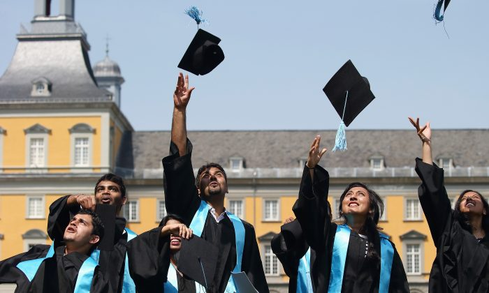Students at a graduation ceremony. Many graduate with unpayable, crippling student debt. (Andreas Rentz/Getty Images)