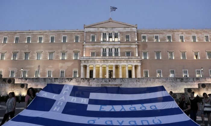 Demonstrators display the Greek flag in front of parliament on July 15, 2015 in Athens, Greece. (Milos Bicanski/Getty Images)