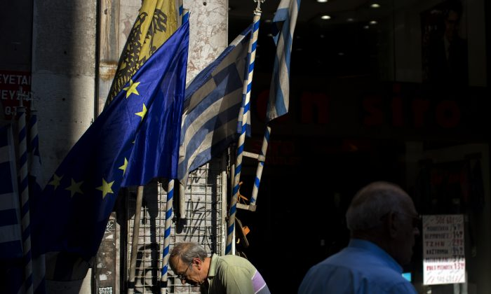 People walk past a shop selling Greek and European Union flags in central Athens, Thursday, July 16, 2015. Greece's troubled left-wing government is seeking urgent relief from European lenders on Thursday, after it pushed a harsh austerity package thought parliament, triggering a revolt in the ruling party and violent demonstrations in central Athens. (AP Photo/Emilio Morenatti)