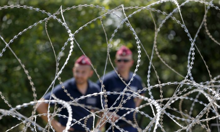 Hungarian police officers guard behind barbed wire near Morahalom, Hungary, Thursday, July 16, 2015. (AP Photo/Darko Vojinovic)