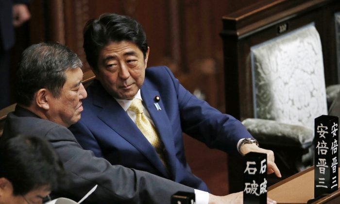 Japanese Prime Minister Shinzo Abe, right, talks to Shigeru Ishiba, the minister for Vitalizing Local Economy in Japan, during a plenary session at the lower house in Tokyo, Thursday, July 16, 2015.  (AP Photo/Shuji Kajiyama)
