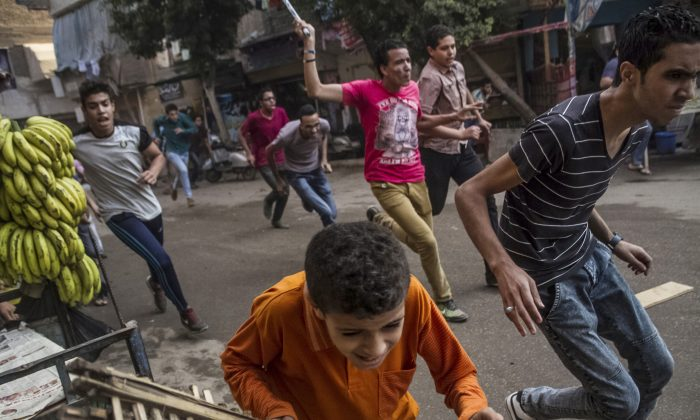 Supporters of the Muslim Brotherhood and bystanders run away from Egyptian security forces during clashes following their protest in the Matariya district of Cairo, Egypt on Tuesday, June 30, 2015.  (AP Photo/Belal Darder)